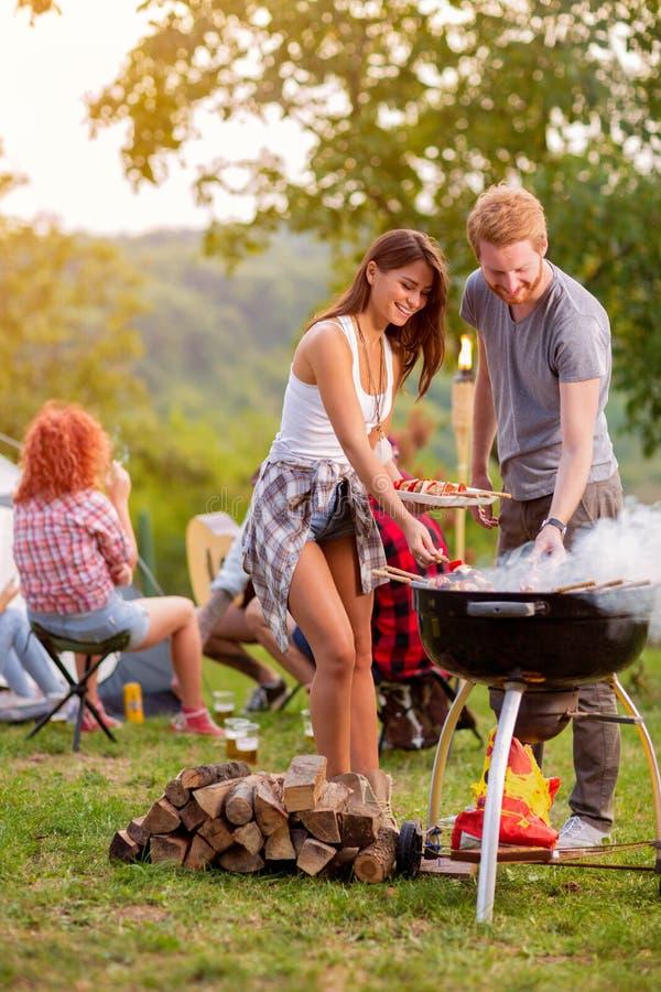 Meisje en jongen die barbecue voorbereiden stock afbeeldingen