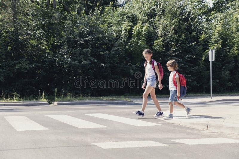 Meisje en jongen die met rugzakken bij de voetgangersoversteekplaats lopen royalty-vrije stock foto