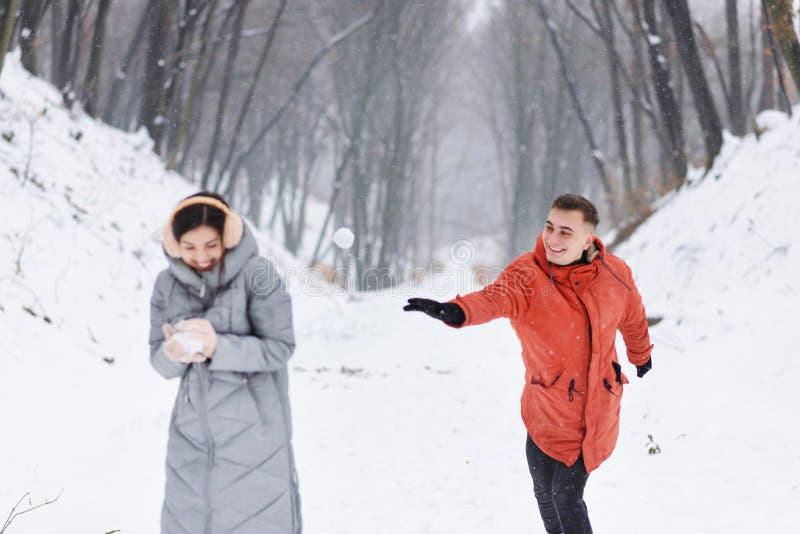 Meisje en Jongen die met Rugzakken Sneeuwballen spelen royalty-vrije stock afbeelding