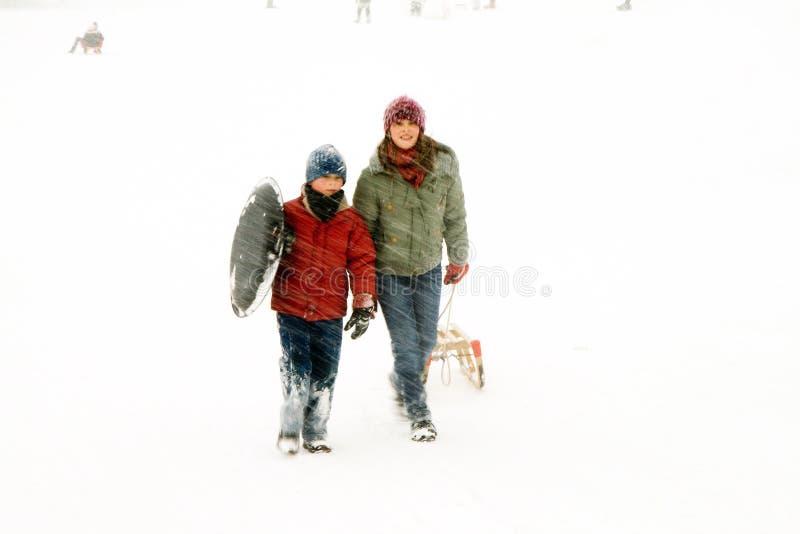 Meisje en jongen die omhoog de heuvel in zware sneeuw lopen royalty-vrije stock afbeelding