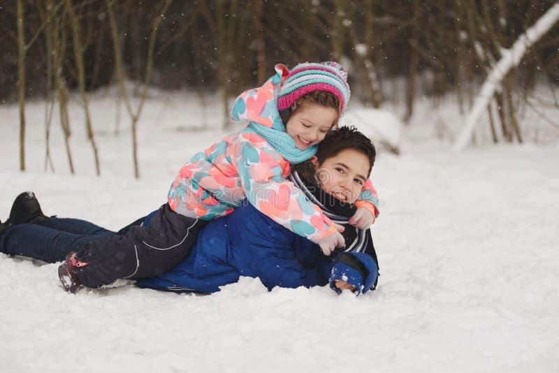 Meisje en jongen die op de sneeuw liggen stock foto