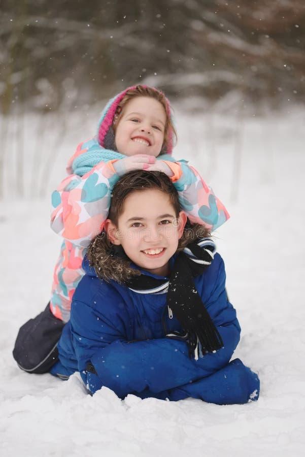 Meisje en jongen die op de sneeuw liggen royalty-vrije stock foto