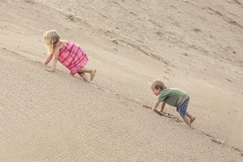 Meisje en jongen die op het Zandduin beklimmen Boom op gebied royalty-vrije stock fotografie