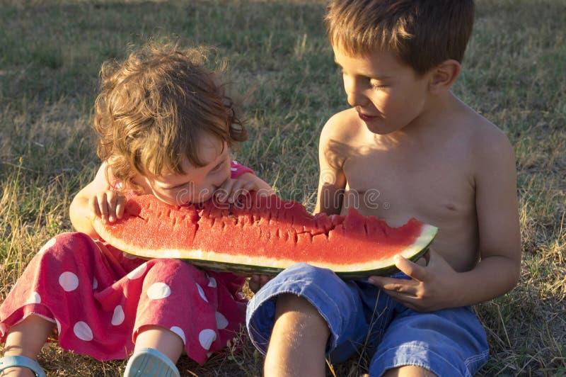 Meisje en jongen die reuzeplak van rijpe watermeloen eten royalty-vrije stock fotografie