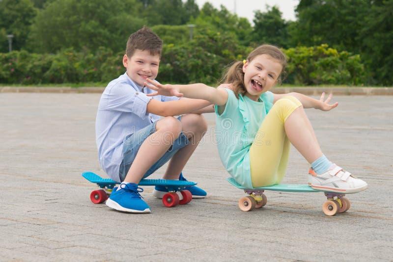 Meisje en jongen in het Park die in openlucht, zitting op sportenraad, de bouw grappige grimassen berijden stock foto