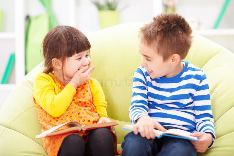 Meisje en jongen lezing en het lachen royalty-vrije stock afbeeldingen
