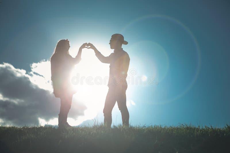 Meisje en jongen in liefde die hart met handen vormen royalty-vrije stock fotografie