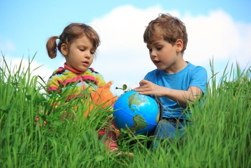 Meisje en jongen met bol op weide stock afbeeldingen