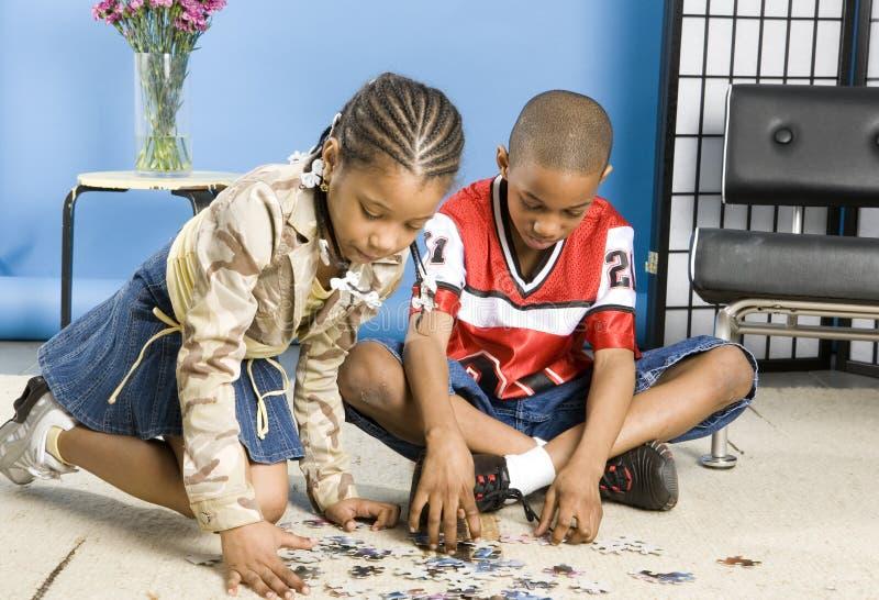 Meisje en jongen met een figuurzaag stock afbeeldingen