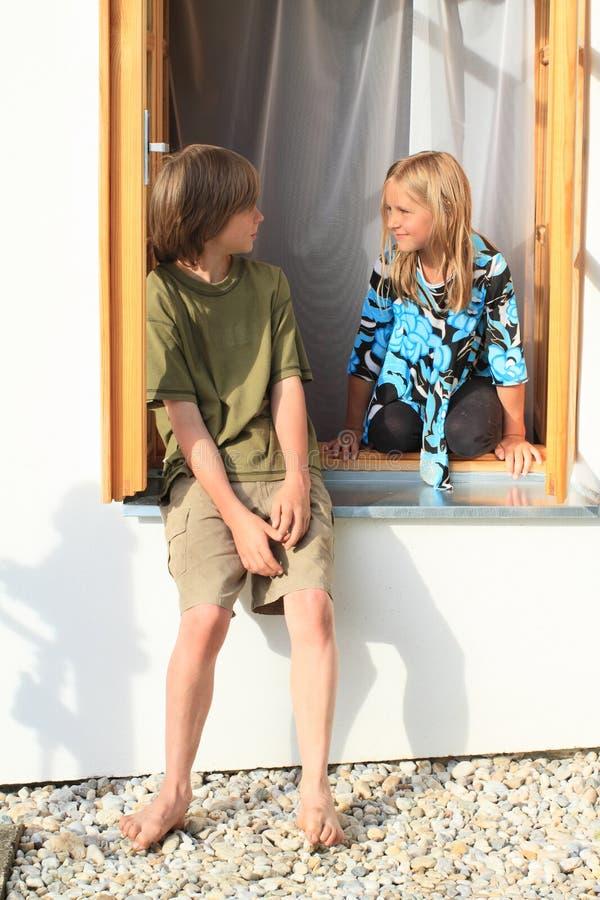 Meisje en jongen op het venster stock fotografie