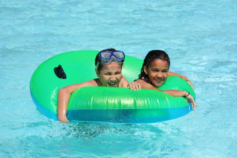 Meisje en Jongen in Pool stock afbeelding
