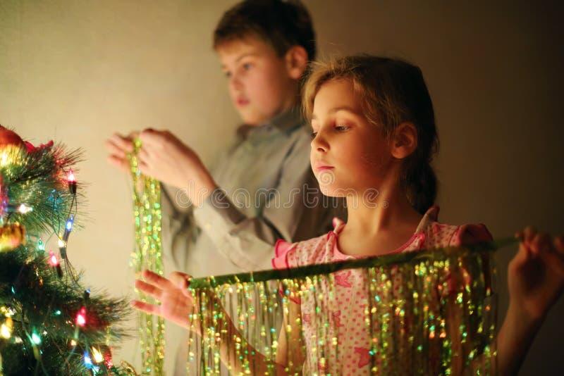 Meisje en jongen verfraaide Kerstboom met klatergoud bij avond stock afbeeldingen