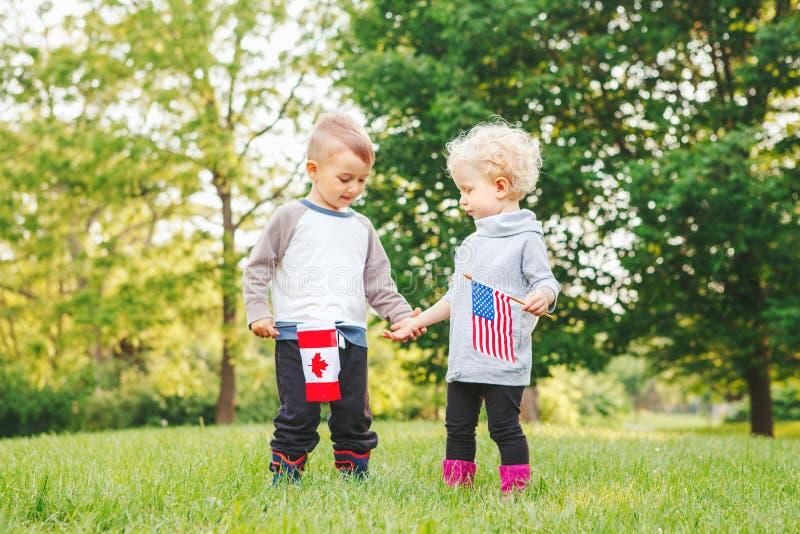 Meisje en jongens het glimlachen het lachen holdingshanden en golvende Amerikaanse en Canadese vlaggen, buitenkant in park stock foto