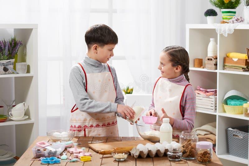 Meisje en jongens het koken in huiskeuken, maakt het deeg voor baksel, gezond voedselconcept royalty-vrije stock afbeeldingen