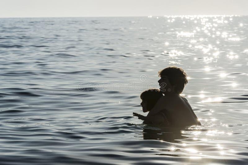 Meisje en jongens het spelen in het overzees in de zomer royalty-vrije stock foto's