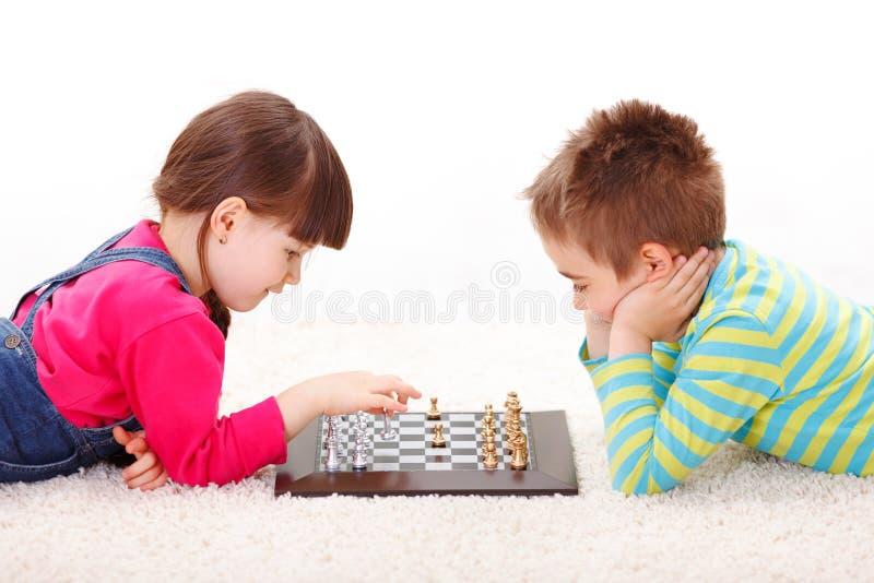 Meisje en jongens het spelen schaak royalty-vrije stock afbeeldingen