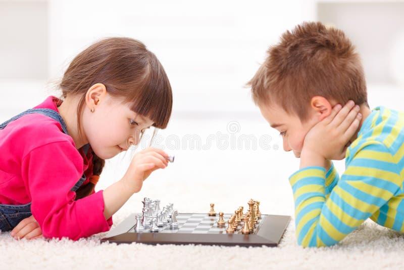 Meisje en jongens het spelen schaak stock afbeeldingen
