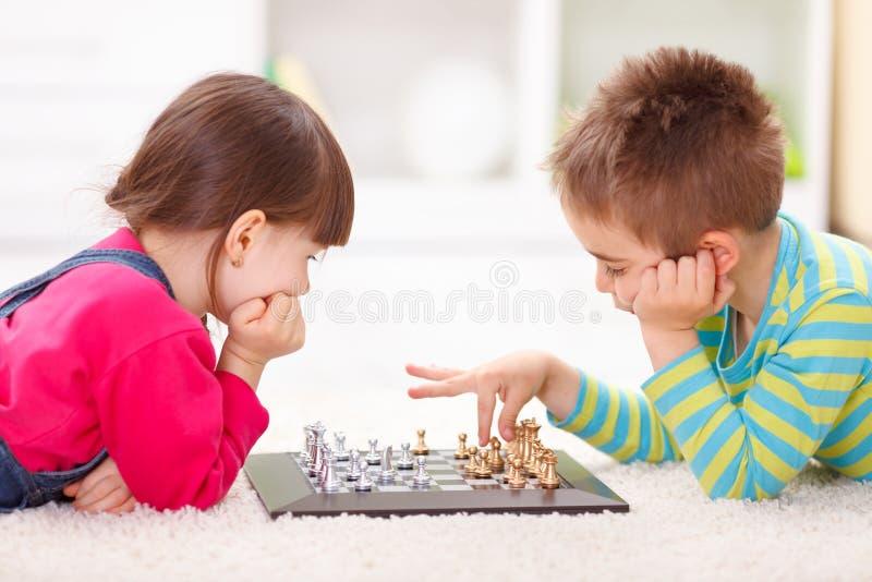Meisje en jongens het spelen schaak stock fotografie