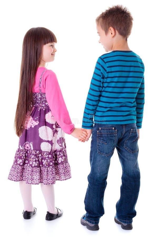 Meisje en jongensholdingshanden stock afbeeldingen