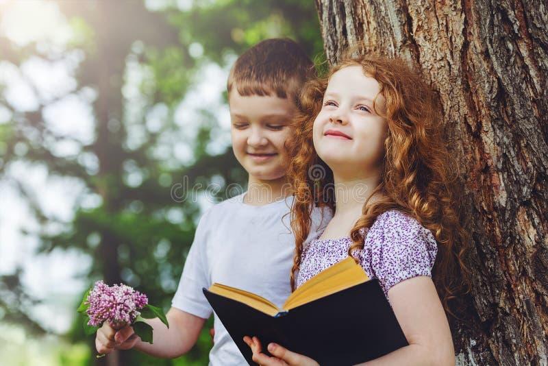 Meisje en jongenslezingsboek in het park stock foto's