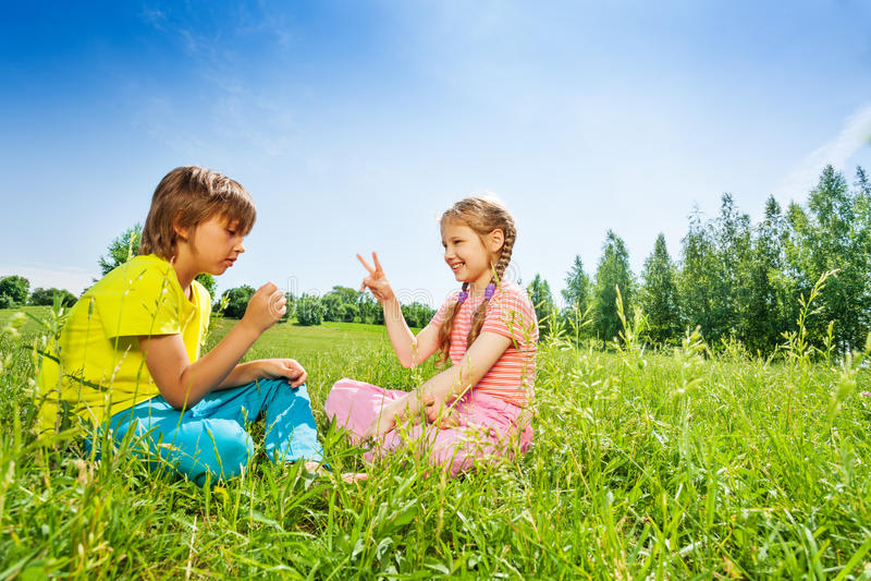 Meisje en jongensspel rots-papier-schaar op gras royalty-vrije stock afbeelding