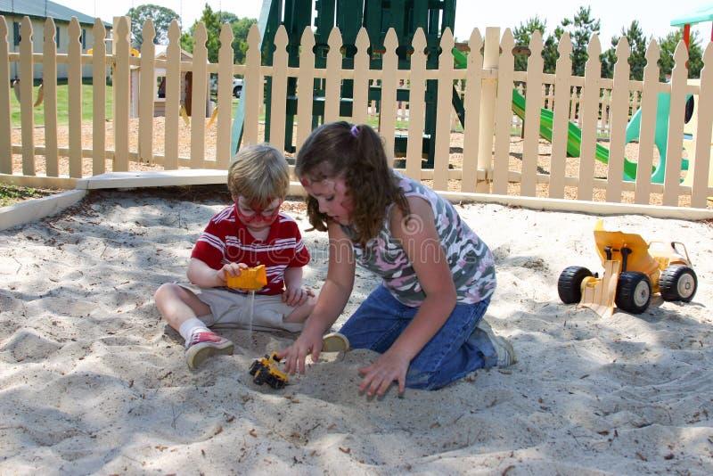 Meisje en jongere jongen met Spider-Man-het spel van de gezichtsverf in zandbak royalty-vrije stock foto
