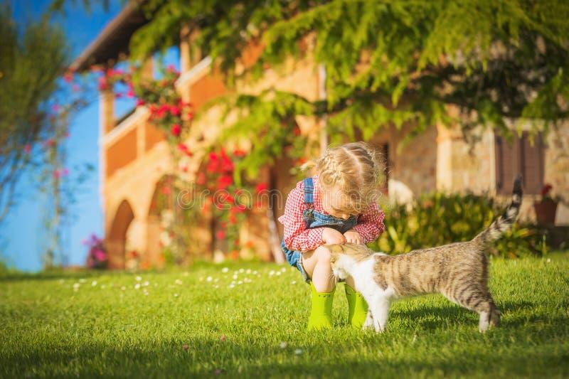 Meisje en kattenspel op een groene weide in de lente mooie D stock fotografie