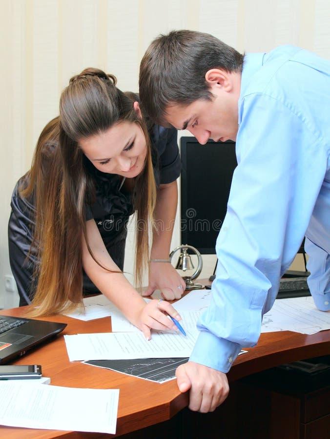 Meisje en mens die in het bureau werken stock foto