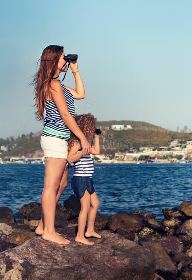 Meisje en moeder die ver weg met verrekijkers kijken royalty-vrije stock afbeelding