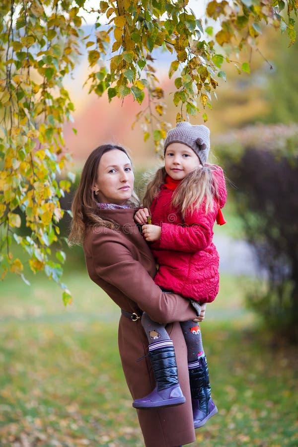 Meisje en moeder in het de herfstpark stock fotografie