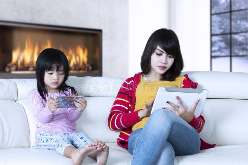 Meisje en moeder het spelen gadgets royalty-vrije stock foto's