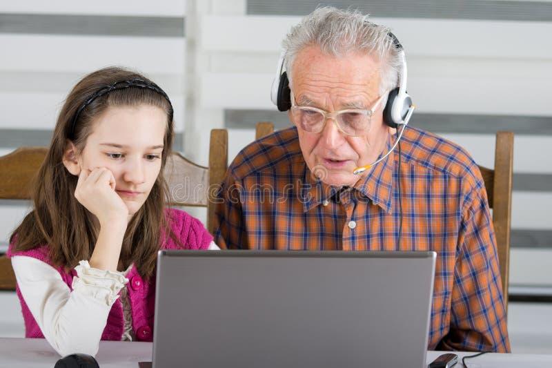 Meisje en oude mens op laptop royalty-vrije stock afbeelding