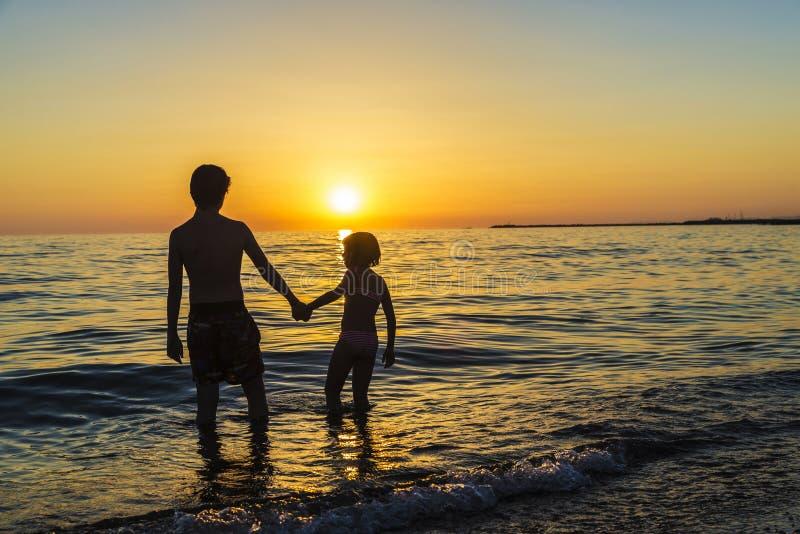 Meisje en tiener het baden op een strand bij zonsondergang stock foto