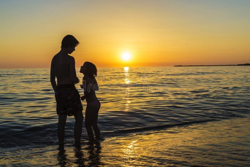 Meisje en tiener het baden op een strand bij zonsondergang stock afbeelding