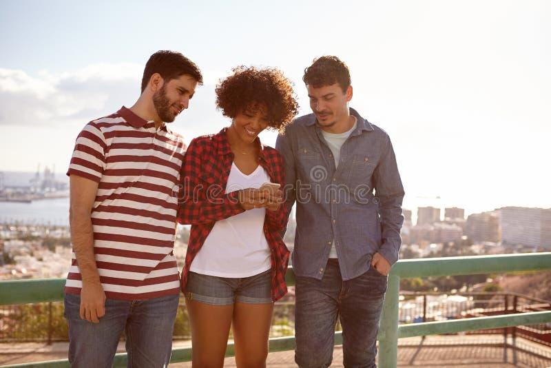 Meisje en twee kerels die berichten lezen stock foto