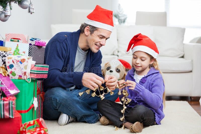Meisje en Vader Holding Christmas Ornaments stock afbeeldingen