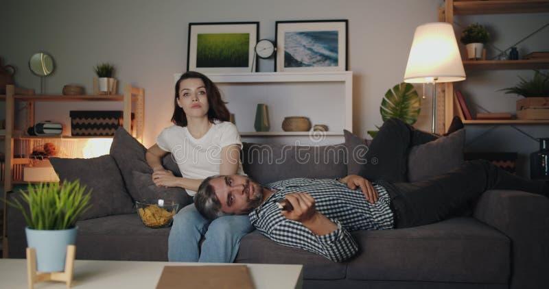 Meisje en vent die 's nachts tv kijkt en knarsetjes op de bank opeet in een donkere kamer stock videobeelden