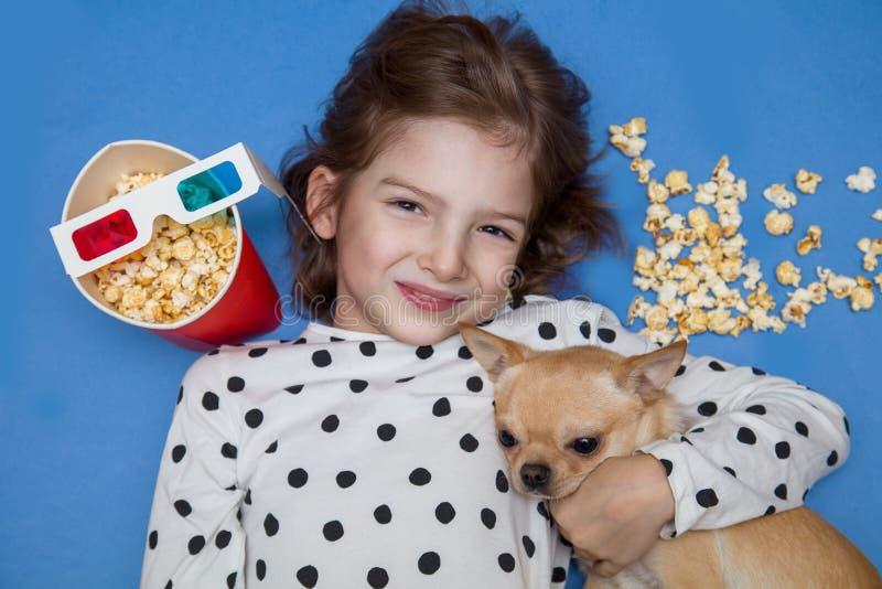 Meisje en weinig hond het letten op film in 3D glazen met popcorn royalty-vrije stock afbeeldingen