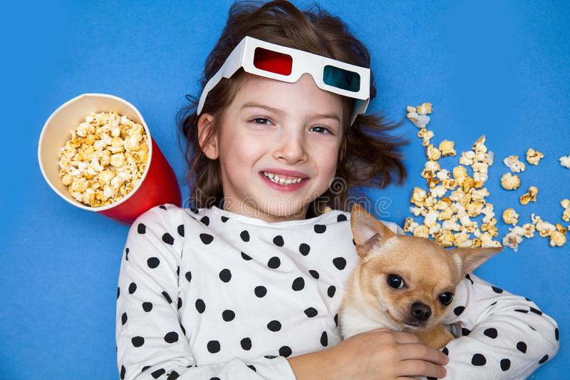Meisje en weinig hond het letten op film in 3D glazen met popcorn royalty-vrije stock foto's