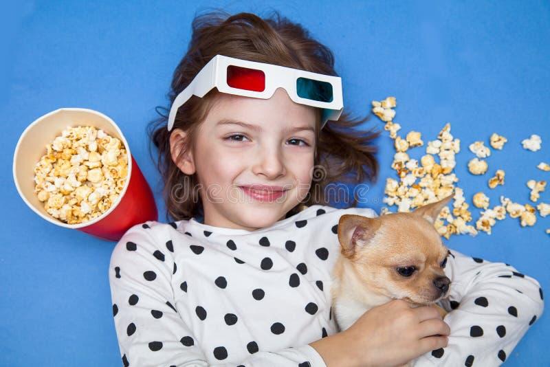 Meisje en weinig hond het letten op film in 3D glazen met popcorn stock foto's