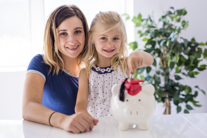 Meisje en zijn moeder die geld opnemen in spaarvarken stock afbeeldingen