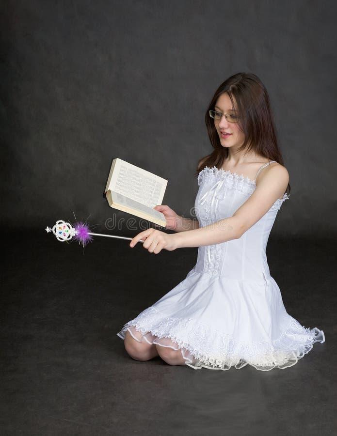 Meisje - fee met toverstokje en boek in handen stock foto's