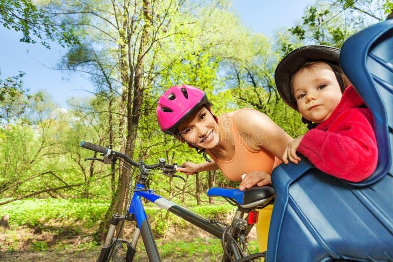 Meisje in fietszetel achter haar sportieve moeder stock foto's