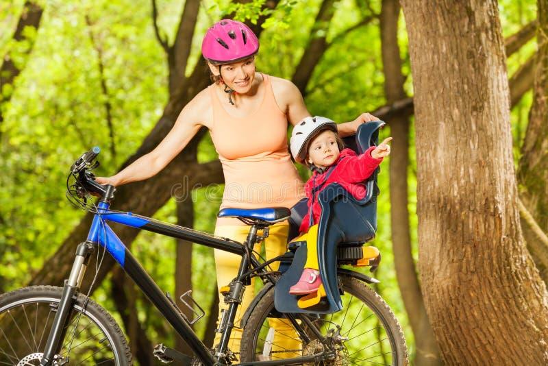 Meisje in fietszetel met moeder tijdens fietsrit stock afbeelding