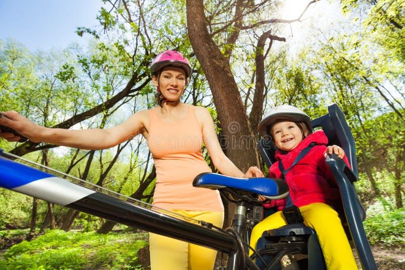 Meisje in fietszetel in openlucht met haar moeder stock fotografie