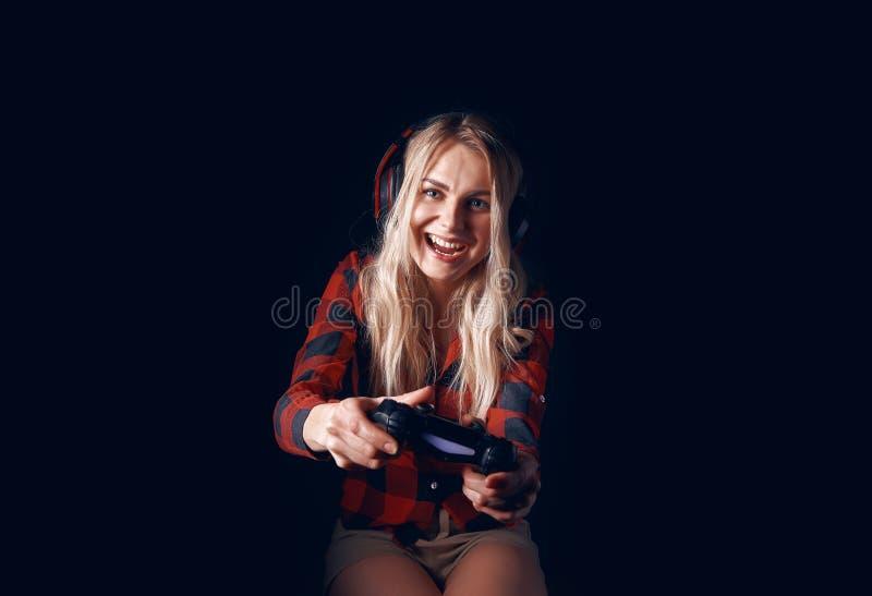 Meisje gamer in hoofdtelefoons en met een bedieningshendel die enthousiast op de console spelen stock fotografie