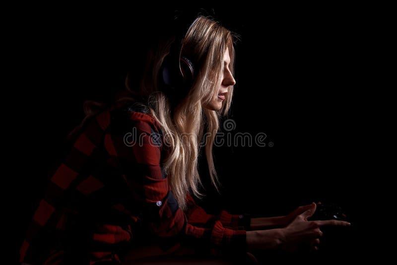 Meisje gamer in hoofdtelefoons en met een bedieningshendel die enthousiast op de console spelen stock foto