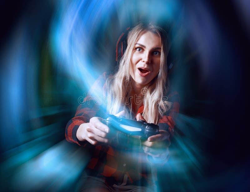 Meisje gamer in hoofdtelefoons en met een bedieningshendel in haar handen die netwerkspelen spelen die aan internationale competi stock fotografie