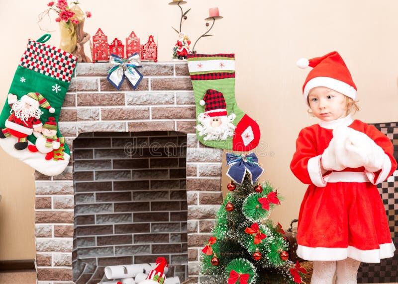 Meisje gekleed kostuum Santa Claus door open haard royalty-vrije stock foto
