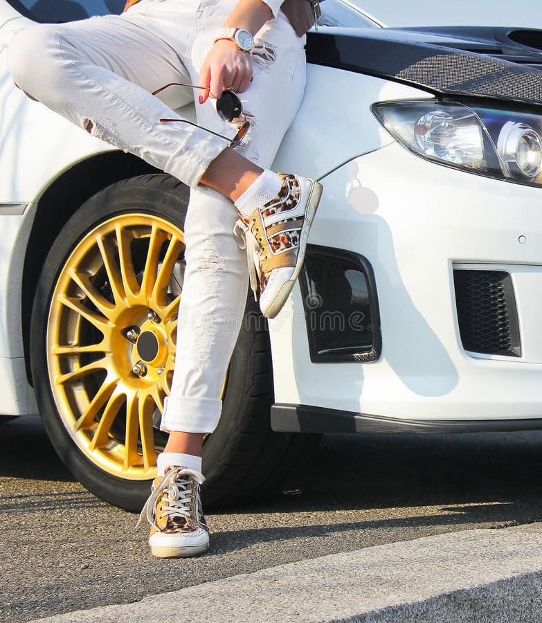 Meisje in gekleurde tennisschoenenschoenen en in witte broeken op achtergrond van witte auto Meisje op autoachtergrond royalty-vrije stock afbeeldingen